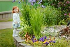 Weinig mooi roodharig meisje van de meisjesbaby bevindt zich binnen dichtbij een vijver royalty-vrije stock afbeelding
