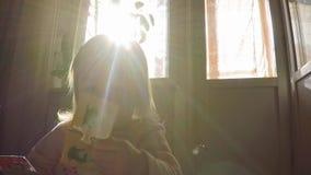 Weinig mooi zoet meisje met blond lang haar trekt raadsels op de achtergrond van de zon, de stralen van de zon over haar stock videobeelden
