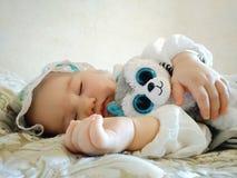 Weinig mooie babyslaap op een beige bed royalty-vrije stock afbeeldingen