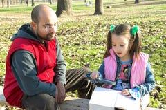 Weinig mooie kind en vader die het boek lezen stock fotografie
