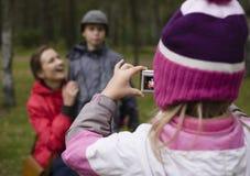 Weinig nakomelingen die zijn familie in park schieten stock foto's