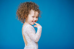 Weinig nieuwsgierig krullend meisje die de camera op blauwe achtergrond bekijken Exemplaar-ruimte Stock Afbeeldingen