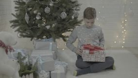 Weinig opgewekte gelukkige jongen het openen doos van de Kerstmis huidige gift in verfraaide nieuwe feestelijke de atmosfeerruimt stock footage