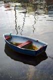 Weinig oude boot op olieachtig water Stock Afbeeldingen