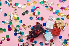 Weinig partij doodde nooit om het even wie Een stuk van chocoladecake met leuke giftdozen en kleurrijke confettien stock fotografie