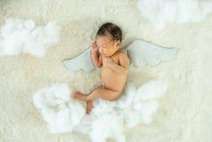 Weinig pasgeboren baby slaapt op wit bed met vleugel bijkomende en pluizige panda's royalty-vrije stock foto