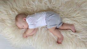 Weinig pasgeboren jongensslaap op een pluizige deken thuis in de slaapkamer stock footage