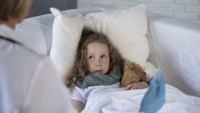 Weinig pati?nt die met vrees de spuit van de verpleegstersholding bekijken, bronchitisbehandeling royalty-vrije stock foto's