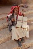 """Weinig Petra, Jordanië †""""20 Juni, 2017: Oude Bedouin mens of Arabische mens in traditionele uitrusting, die zijn muzikaal instr Stock Afbeelding"""