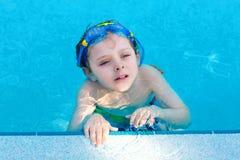Weinig peuterjong geitjejongen die de concurrentiesport maken zwemmen Jong geitje met zwemmende beschermende brillen die rand van stock foto's