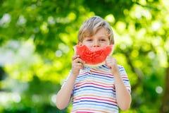 Weinig peuterjong geitjejongen die watermeloen in de zomer eten royalty-vrije stock afbeeldingen