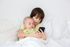 Weinig peuterjongen die in bed met zijn babybroer leggen, playin royalty-vrije stock afbeelding