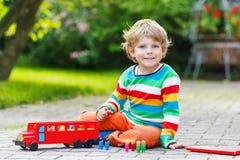 Weinig peuterjongen die met autostuk speelgoed spelen Stock Afbeelding
