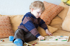 Weinig peuterjongen die met houten speelgoed speelt Stock Foto