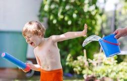 Weinig peuterjongen die pret met het bespatten van water in de zomergeep hebben Stock Foto