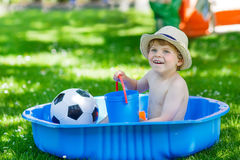 Weinig peuterjongen die pret met het bespatten van water in de zomergeep hebben Stock Fotografie
