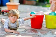 Weinig peuterjongen die pret met het bespatten van water in de zomergeep hebben Royalty-vrije Stock Foto