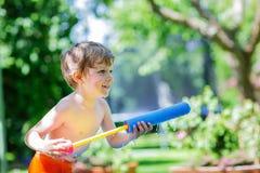 Weinig peuterjongen die pret met het bespatten van water in de zomergeep hebben Royalty-vrije Stock Afbeeldingen