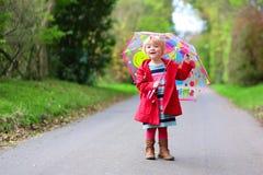 Weinig peutermeisje die met paraplu lopen Stock Foto