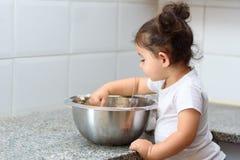 Weinig peutermeisje het kneden deeg in keuken stock afbeeldingen