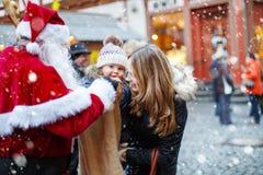 Weinig peutermeisje met moeder op Kerstmis Stock Foto's