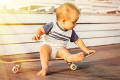 Weinig peuterzitting blootvoets op skateboard die zich op houten bestrating in zonstralen bevinden openlucht De zomeractiviteit e stock foto's