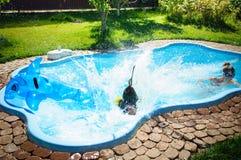 Weinig pretmeisje is sprong en zwembad in de zomer Stock Foto's