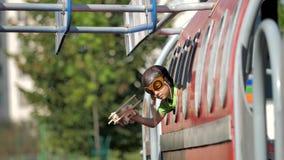 Weinig proef met vliegeniersmateriaal het spelen met houten vliegtuigstuk speelgoed op vliegtuigvenster stock video