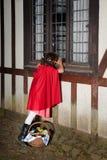 Weinig rode berijdende kap die door venster kijkt royalty-vrije stock afbeelding