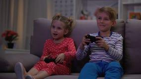 Weinig ronde van het jongens winnende videospelletje, zuster verstoord krijgen, speelt de concurrentie stock footage