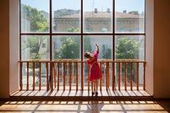 Weinig Russisch ballerinameisje in de traditionele oefening van de kledingsstaaf dichtbij venster stock foto