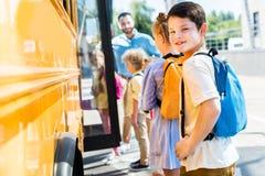 weinig schooljongen die schoolbus met klasgenoten ingaan terwijl leraar status royalty-vrije stock afbeeldingen