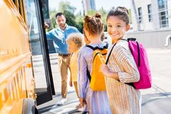 weinig schoolmeisje dat schoolbus met klasgenoten ingaat terwijl leraar status stock foto