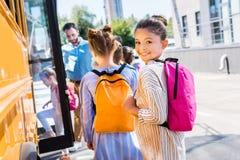 weinig schoolmeisje dat schoolbus met klasgenoten ingaat terwijl leraar status stock fotografie