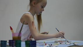 Weinig schoolmeisje De leuke meisjeschilder trekt op de lijst en op zich aangaande haar kleren Langzame Motie stock footage