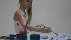 Weinig schoolmeisje De leuke meisjeschilder trekt op de lijst en op zich aangaande haar kleren Langzame Motie stock videobeelden