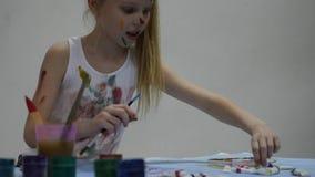 Weinig schoolmeisje De leuke meisjeschilder trekt op de lijst en op zich aangaande haar kleren Langzame Motie stock video