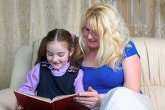 Weinig schoolmeisje en moeder die homeworks doen Stock Foto's