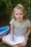 Weinig schoolmeisje zit hebben gekruistd benen onder een boom en houdt op overlapping een open notitieboekje Stock Foto's