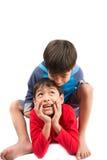 Weinig sibling de jongens zitten en spelen samen op witte achtergrond stock afbeeldingen