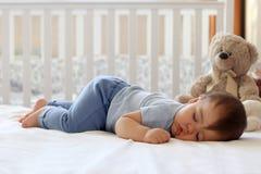 Weinig slaap van de babyjongen op maag stock afbeelding