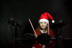 Weinig slagwerker die als Santa Claus wordt vermomd die de elettronic trommeluitrusting spelen Royalty-vrije Stock Foto