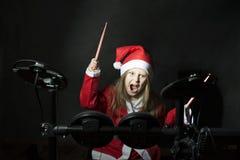 Weinig slagwerker die als Santa Claus wordt vermomd die de elettronic trommeluitrusting spelen Stock Fotografie