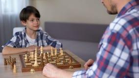 Weinig slim jongens winnend schaak, handenschudden met zijn trotse vader, hobby stock video