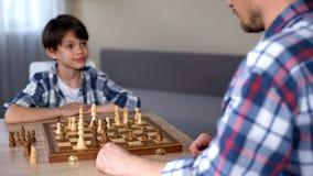 Weinig slim spel die van het jongens winnend schaak, gelukkig vader, favoriete hobby bekijken stock fotografie
