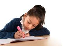 Weinig Spaans vrouwelijk kind die en thuiswerk met roze teller schrijven doen Stock Foto's