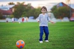 Weinig speelvoetbal en voetbal van de peuterjongen, die pret hebben overtreffen Stock Foto