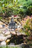 Weinig standbeeld van de zitting Boedha in de tuin Stock Fotografie