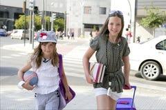 Weinig studentenmeisjes die naar school in stad gaan Stock Foto's
