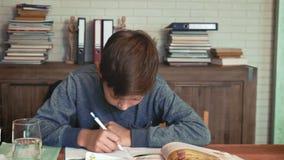 Weinig taak van de jongenslezing van zijn handboek en het neerschrijven van iets stock video